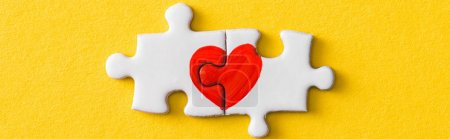 Photo for Panoramic shot of connected jigsaw puzzle pieces with drawn red heart isolated on yellow - Royalty Free Image