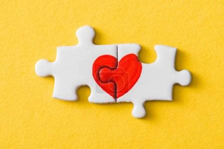 Photo for Top view of connected puzzle pieces with drawn red heart isolated on yellow - Royalty Free Image