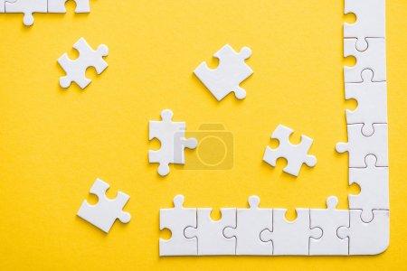 Photo pour Vue du haut des pièces de puzzle connectées incomplètes près de la ligne finie isolée sur le jaune - image libre de droit