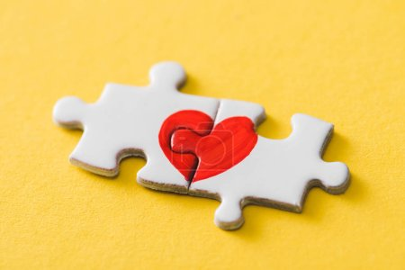 Photo for Connected puzzle pieces with drawn red heart on yellow - Royalty Free Image