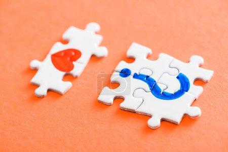 Foto de Selective focus of connected puzzle pieces with drawn red heart and blue question mark on orange - Imagen libre de derechos