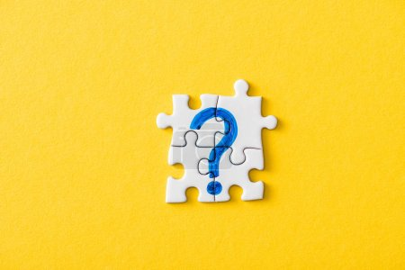 Foto de Top view of connected puzzle pieces with drawn blue question mark on yellow - Imagen libre de derechos