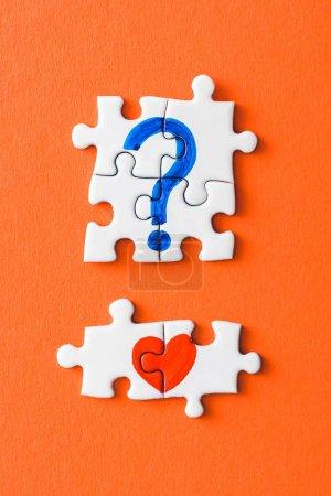 Foto de Top view of connected puzzle pieces with drawn red heart and blue question mark on orange - Imagen libre de derechos