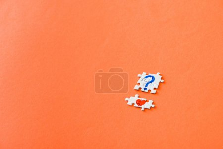 Foto de Top view of small connected puzzle pieces with drawn red heart and blue question mark on orange - Imagen libre de derechos