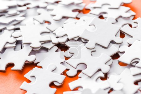 Photo for Selective focus of incomplete white jigsaw puzzle pieces on orange - Royalty Free Image