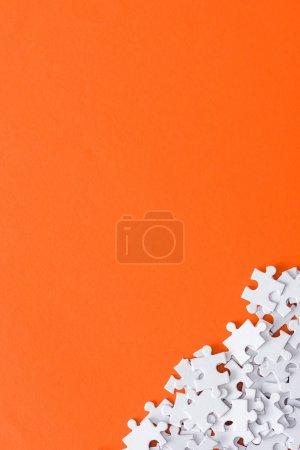 Foto de Top view of unfinished puzzle pieces isolated on orange with copy space - Imagen libre de derechos