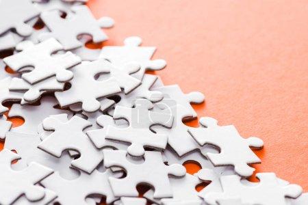 Photo pour Mise au point sélective des pièces de puzzle blanc inachevés sur l'orange - image libre de droit