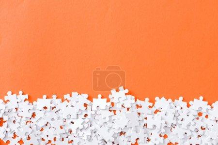Foto de Vista superior de piezas de rompecabezas blanco inacabadas aisladas en naranja con espacio de copia - Imagen libre de derechos