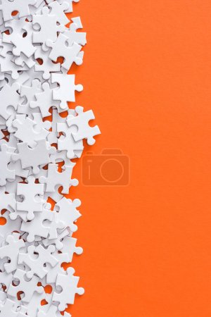 Photo for Top view of unfinished white jigsaw puzzle pieces isolated on orange with copy space - Royalty Free Image