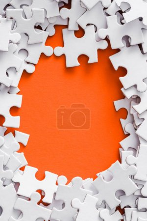 Ansicht des Rahmens aus weißen Puzzleteilen auf Orange mit Kopierraum