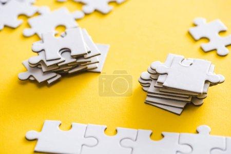 Photo pour Mise au point sélective de pièces de puzzle connectées et inachevées sur le jaune - image libre de droit