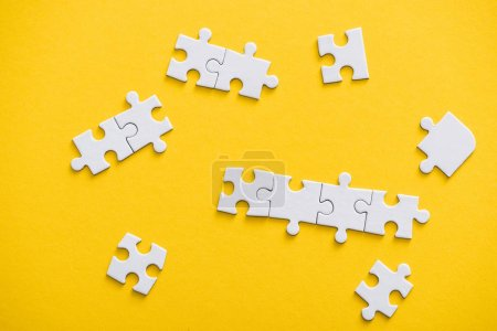 Photo pour Top view of connected and unfinished puzzle pieces isolated on yellow - image libre de droit