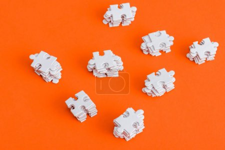 Photo for Top view of stacked white puzzle pieces on orange - Royalty Free Image