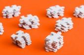 """Постер, картина, фотообои """"top view of stacked white puzzle pieces on orange"""""""