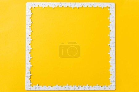 Photo pour Vue de dessus du cadre avec des pièces de puzzle blanc connecté isolé sur jaune - image libre de droit