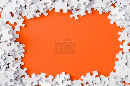 Photo for Top view of frame with white jigsaw puzzle pieces isolated on orange - Royalty Free Image