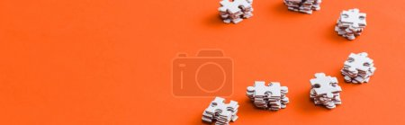 Photo for Panoramic shot of stacks with white puzzle pieces on orange - Royalty Free Image