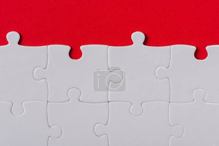 Photo for Top view of matched white jigsaw puzzle pieces isolated on red - Royalty Free Image