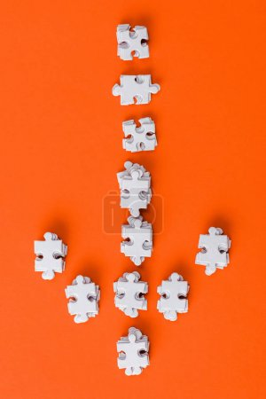 Photo for Top view of white direction arrow with puzzle pieces on orange - Royalty Free Image