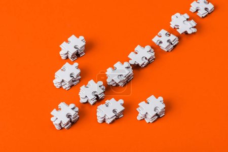 Photo for Top view of direction arrow with white jigsaw puzzle pieces on orange - Royalty Free Image