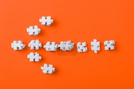 Photo for Top view of white direction arrow with jigsaw puzzle pieces on orange - Royalty Free Image
