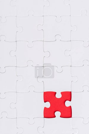 Photo for Top view of white connected puzzles with red shape - Royalty Free Image