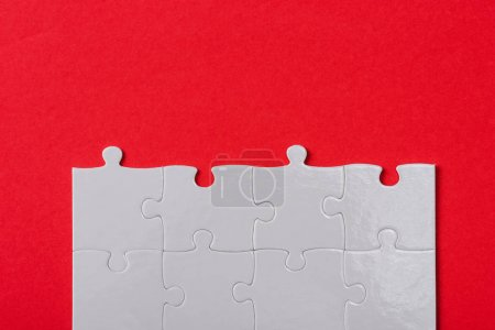 Photo for Top view of connected white jigsaw puzzle pieces isolated on red - Royalty Free Image