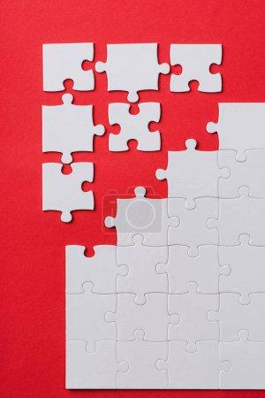 Photo pour Vue du haut de blanc connecté et séparé puzzle pièces isolées sur rouge - image libre de droit
