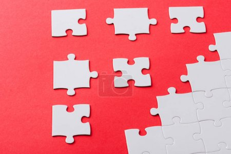 Photo for White connected and separate jigsaw puzzle pieces isolated on red - Royalty Free Image