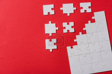 Photo for Top view of connected and separate jigsaw puzzle pieces isolated on red - Royalty Free Image