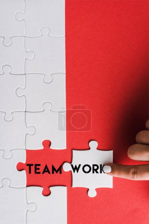 Photo for Top view of woman pointing with finger at jigsaw near connected puzzle pieces with teamwork lettering on red - Royalty Free Image