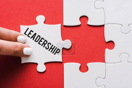 Photo for Top view of woman touching jigsaw with leadership lettering near connected white puzzle pieces on red - Royalty Free Image