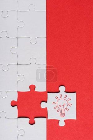 Photo for Top view of incomplete jigsaw near white puzzle piece with light bulb isolated on red - Royalty Free Image