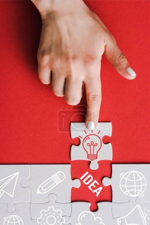 Photo for Top view of woman pointing with finger at jigsaw with light bulb near connected white puzzle pieces and idea lettering on red - Royalty Free Image