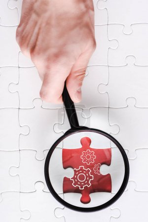 top view of man holding magnifying glass near jigsaw with gears settings near white connected puzzle pieces