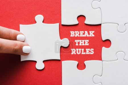 Photo pour Top view of woman touching jigsaw near break the rules lettering and connected white puzzle pieces and idea lettering on red - image libre de droit