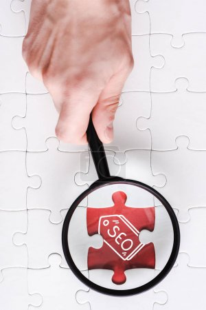 Photo pour Top view of man holding magnifying glass near jigsaw with seo lettering near white connected puzzle pieces - image libre de droit