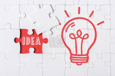 Photo pour Vue du haut du puzzle incomplet blanc près de la pièce de puzzle et du lettrage d'idée et de l'ampoule - image libre de droit