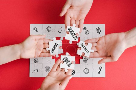 Photo pour Top view of man and woman holding white puzzle pieces with creative, idea, business and success words on white - image libre de droit