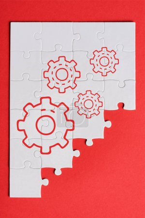 Photo pour Top view of white connected puzzle pieces with gears settings isolated on red - image libre de droit
