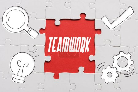 Photo for Top view of connected jigsaw puzzle pieces near teamwork letters - Royalty Free Image