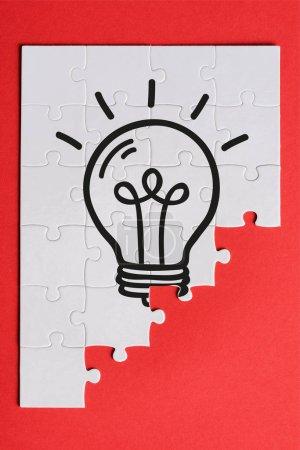Photo pour Vue supérieure des pièces blanches reliées de puzzle avec l'ampoule d'ampoule d'isolement sur le rouge - image libre de droit