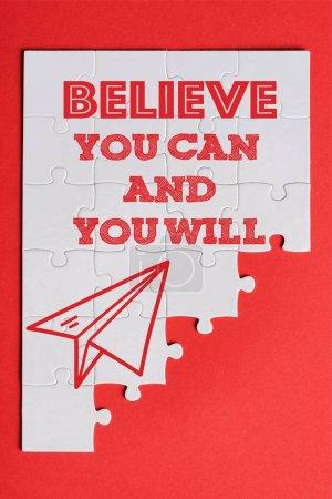 Photo pour Vue du haut des pièces blanches de puzzle connectés avec le plan de papier et croyez que vous pouvez et vous lettron isolément sur le rouge - image libre de droit