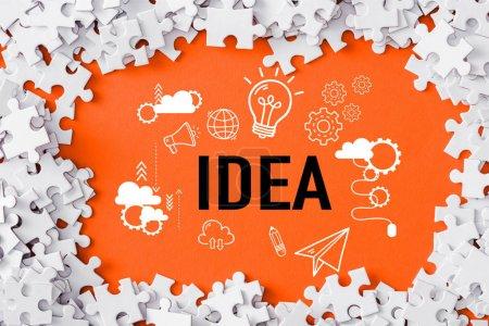 Photo pour Vue supérieure du cadre des pièces blanches de puzzle autour du lettrage d'idée sur l'orange - image libre de droit