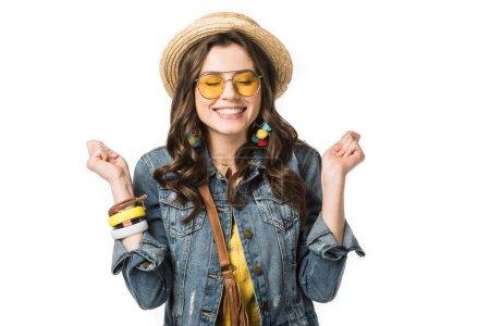 Photo pour Excité fille boho dans plaisancier et lunettes de soleil tenant les poings vers le haut avec les yeux fermés isolé sur blanc - image libre de droit