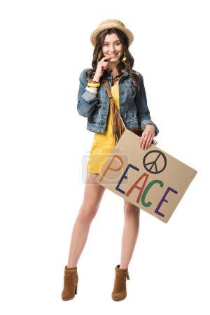Photo pour Vue pleine longueur de fille hippie souriante en chapeau de paille tenant la plaque avec l'inscription isolée sur blanc - image libre de droit