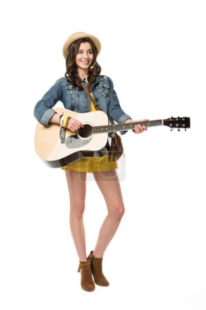 Photo for Full length view of smiling boho girl playing acoustic guitar isolated on white - Royalty Free Image
