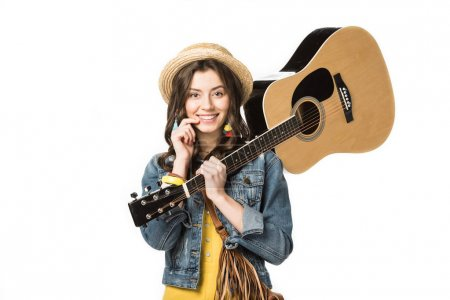 Photo pour Smiling hippie girl holding acoustic guitar isolated on white - image libre de droit