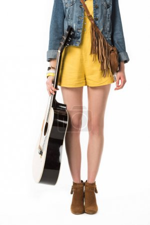 Photo pour Vue recadrée de fille de boho retenant la guitare acoustique d'isolement sur le blanc - image libre de droit