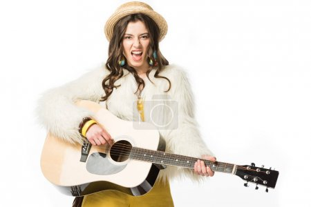 Photo for Excited boho girl in straw hat playing acoustic guitar isolated on white - Royalty Free Image